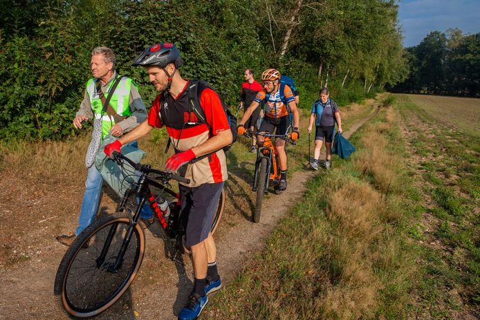 Mountainbikers trekken door de bossen in het Rijk van Nijmegen om zwerfafval op te ruimen. Voormalig olympisch kampioen Bart Brentjens (oranje shirt en helm) helpt mee.