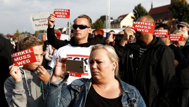 Extreem-rechtse betogers protesteren met 'rode kaarten' tegen bondskanselier Merkel bij een gebouw in Wismar waar zij spreekt. Beeld null