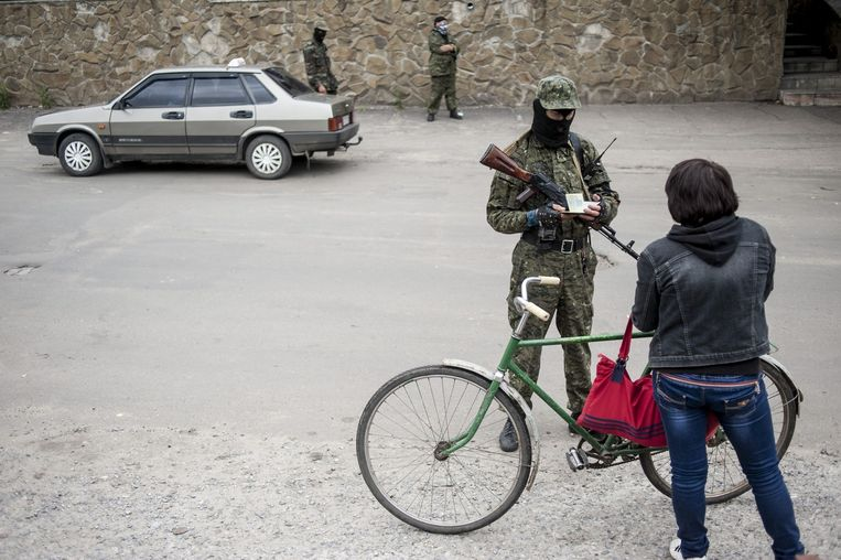Een separatist controleert de papieren van een vrouw die Slavjansk wil verlaten. Beeld AP