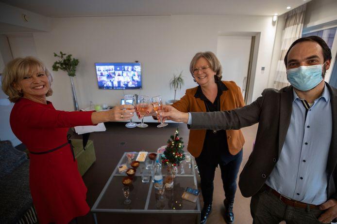 Laurence Oostveen, Jolande Kraneveld en Bas Goossen (vlnr) brengen in het Slimste Huis bij het Evoluon een toast uit tijdens de kerstborrel, met op de achtergrond de online deelnemers.