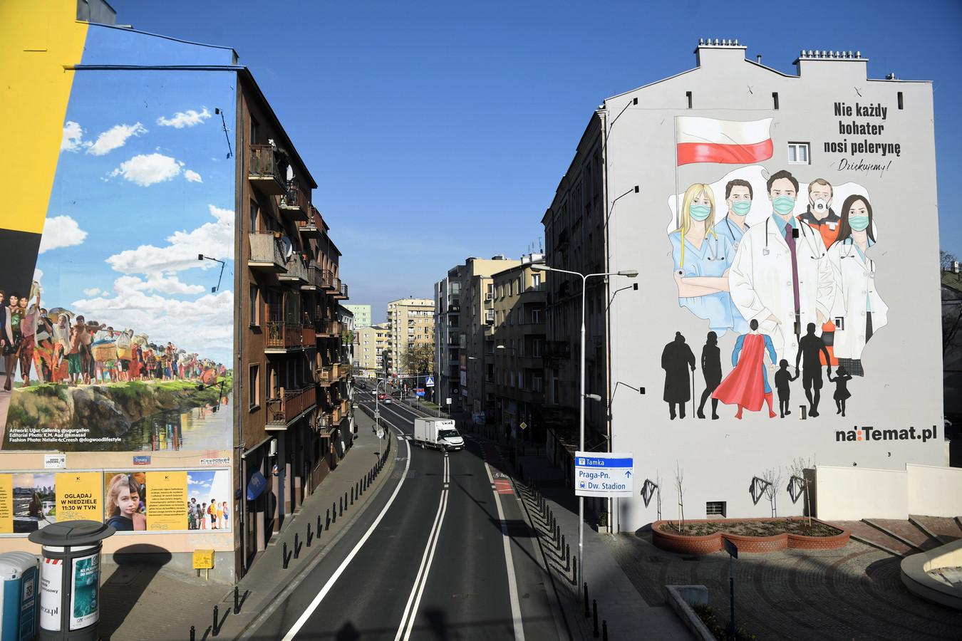Een muurschildering met de tekst 'Niet alle superhelden dragen capes' bij een beeld van hulpverleners in Warschau, Polen.