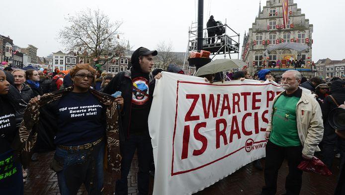Tegenstanders van Zwarte Piet voeren actie tijdens de intocht van Sinterklaas in Gouda