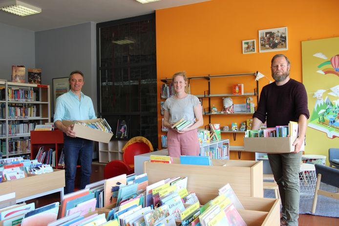 Schepen Joris Vandenhoucke, Marlies Decavel van de bib en opbouwwerker Piet Clottens met de boekjes.