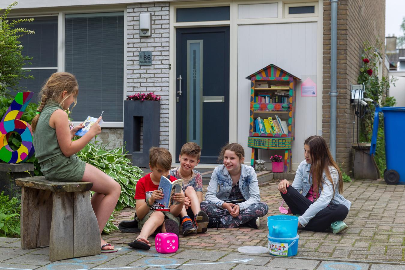 Feline Soetens leest buurtgenootjes een verhaaltje voor tijdens de Dag van de Minibieb in Veldhoven