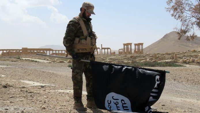 Een Syrische soldaat houdt een IS-vlag vast na de herovering van de stad.