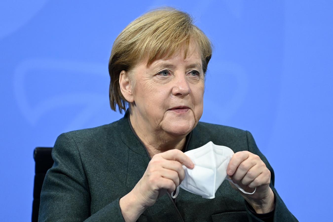De Duitse bondskanselier Angela Merkel zet haar FFP2-mondmasker weer op na een persconferentie.