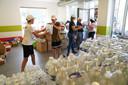 Leden van de kajakvereniging van Anseremme vormen een ketting om al het flessenwater uit de vrachtwagen te laden.