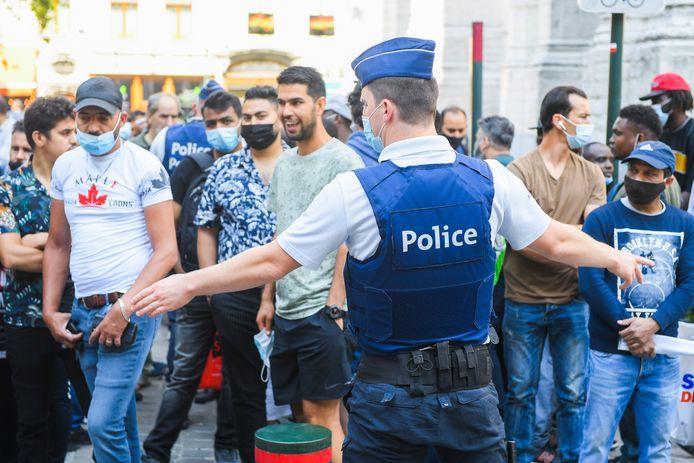 """Plusieurs centaines de personnes se sont rassemblées vendredi, à compter de 06h00, devant l'espace aménagé en """"zone neutre"""" rue Melsens à Bruxelles, à proximité de l'église du Béguinage, l'un des trois sites où a pris place la grève de la faim des sans-papiers"""