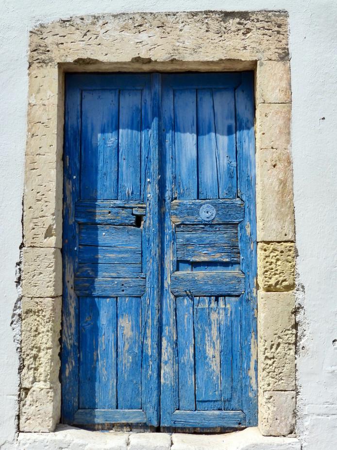 Het is net een schilderijtje: deze prachtige oude blauwe deur op Kreta. Wie goed kijkt, spot er veel meer.