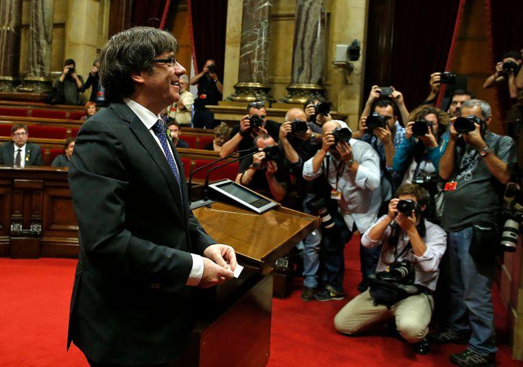 Carles Puigdemont loopt, onder belangstelling van fotografen, naar de voorzitter van het Catalaanse parlement om zijn stem uit te brengen. Beeld AP