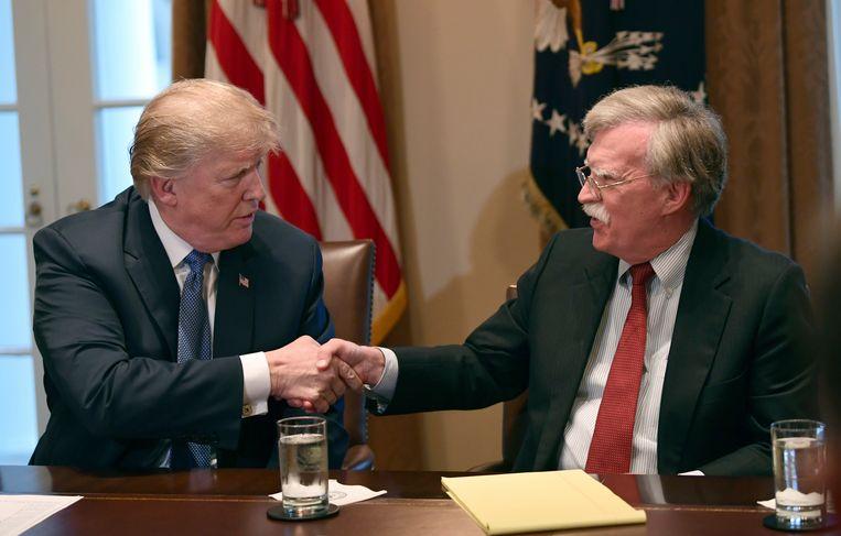 President Donald Trump schudt zijn nationale veiligheidsadviseur John Bolton de hand, 9 april 2018. Afgelopen zomer ontsloeg Trump hem. Beeld AP