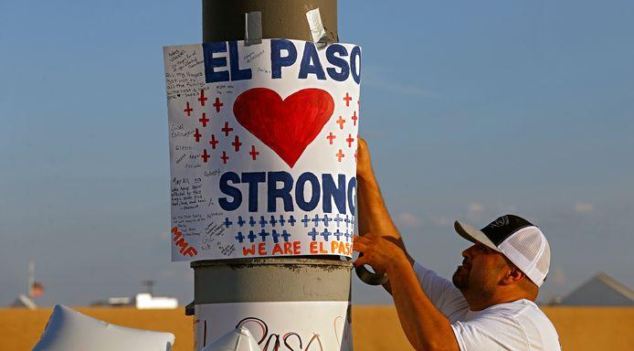 Een man hangt een poster op bij een monument voor de slachtoffers van de schietpartij in El Paso.