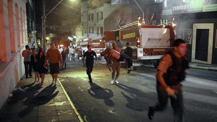 Een man draagt een gewonde naar buiten, nadat brand uitbrak in een club in Santa Maria, Brazilië. Bij de brand vielen ruim 200 doden, zo wordt gemeld. Beeld EPA