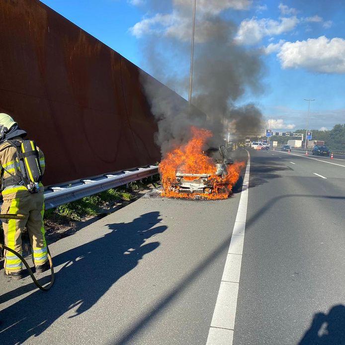 De vlammen slaan uit de auto.