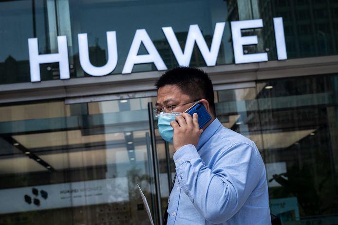 Een man loopt bellend voorbij een winkel van Huawei  in de Chinese hoofdstad Peking.