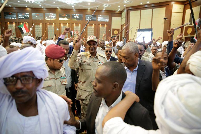 Generaal Mohamed Hamdan Dagalo, bijgenaamd Hemedti (midden) laat zich in Khartoem door aanhangers toejuichen terwijl hij met zijn stok zwaait. Hij profileert zich steeds meer als de opvolger van afgezette dictator Al Bashir.   Beeld   EPA/MARWAN ALI