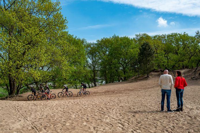 Wandelaars kijken toe hoe mountainbikers door het mulle zand heen ploegen.