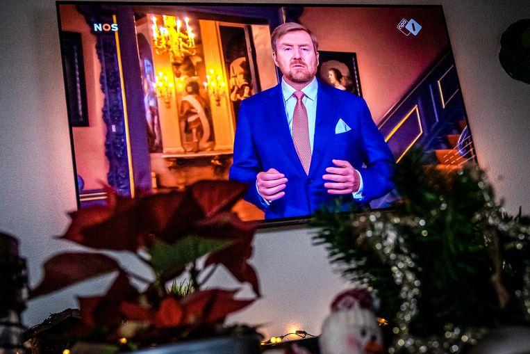 Kijken naar koning Willem-Alexander op televisie tijdens zijn kersttoespraak. Beeld ANP