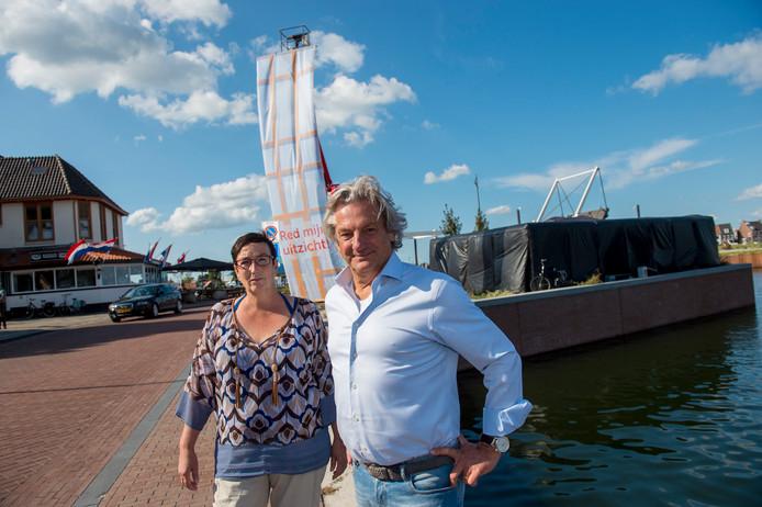 Red mijn uitzicht (hier Helen Meijer en Peter de Vries) protesteren tegen de toekomstige hoogbouw. Het doek geeft de hoogte aan van het te bouwen Café de Liefde.