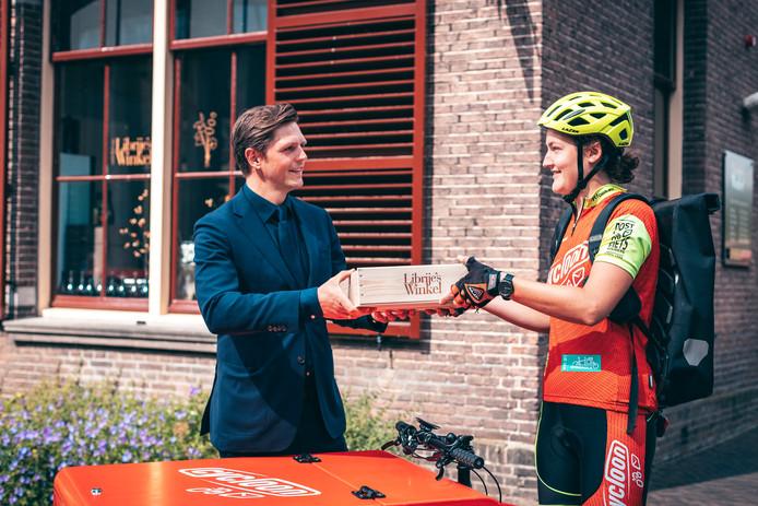 Matthias van Nieuwland overhandigt symbolisch een pakket uit Librije's Winkel aan een fietskoerier van Cycloon. Vanaf nu bezorgen die overal in Nederland op duurzame wijze.