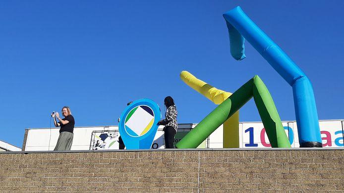 De Norbertus Gertrudis Mavo in Roosendaal onthult de pinpoint die de verhuizing markeert. Links directeur Kiki Nieuwkerk.