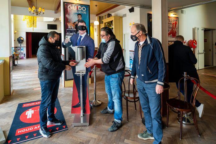 Said El Hassnaoui (links) en zijn maat Mike Doulis ontsmetten, onder toeziend oog van directeur Roel Coppelmans, hun handen alvorens ze op weg gaan naar de zaal van het Posttheater om daar de voorstelling DNA van cabaretier Peter Pannekoek bij te wonen.