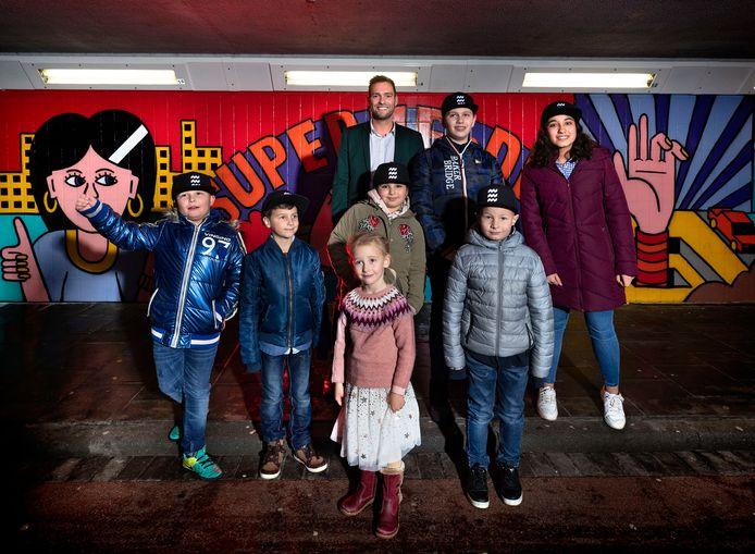 Wethouder Rik Thijs met (vlnr) Dean Bosch (9 jaar), Ryan Adam (8), Izis Jacobs (5), Iman Al Baz (9), Rommy Hopman (15), Daan Kluijtmans (6) en Irazgül Sayar in het tot 'heldentunnel' omgevormde Kruisstraattunneltje.