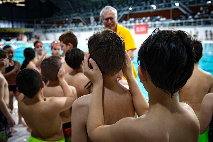 Leerlingen van De Korenaar luisteren in het zwemstadion in Eindhoven naar de uitleg van Jos de Greef van de Eindhovense Reddingsbrigade.