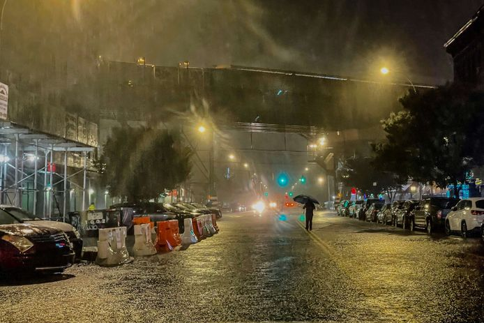 Een persoon in de gieten de regen op straat in stadsdeel The Bronx in New York City.