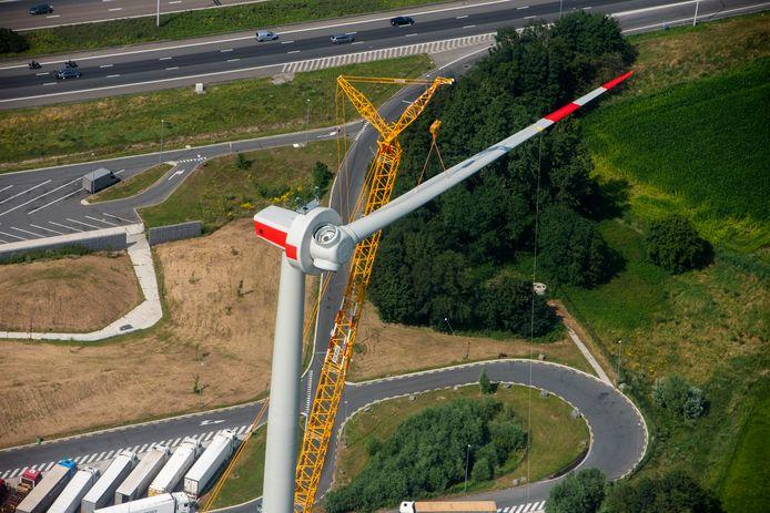De wieken aan de windmolen langs de E17 in Kalken worden gemonteerd.