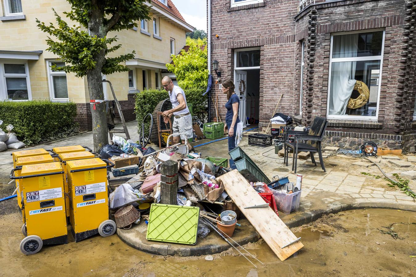 Inwoners ruimen puin na de wateroverlast in Valkenburg aan de Geul. De hevige regenval en overstromingen in Limburg hebben voor veel schade gezorgd.