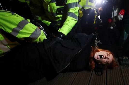 Agenten werken een vrouw tegen de grond bij de herdenkingsbijeenkomst voor de vermoorde Sarah Everard. Vier vrouwen werden gearresteerd bij de wake.