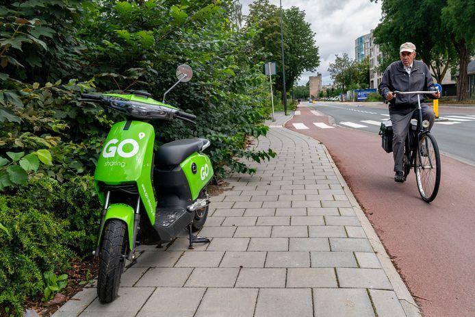 Een scooter van Go Sharing geparkeerd tegen de heg op de Kooikersweg in de Kruiskamp.
