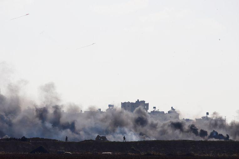 Israëlische soldaten patrouilleren aan de grens tussen Israël en Gaza, terwijl er rook te zien is in de Gazastrook. Beeld Reuters