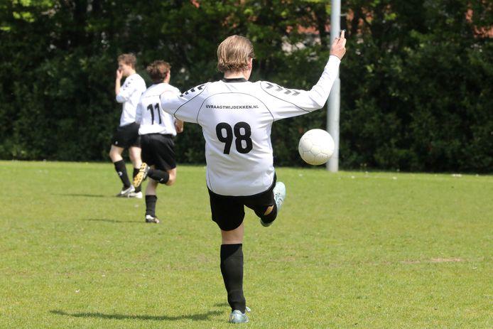 De nummer 98 van Overasseltse Boys trapt een bal weg.