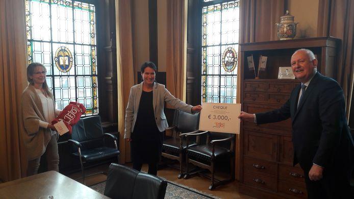 Jolande van Meer (links) en Ingrid de Vries van TEJO ontvangen een cheque van 3000 euro van oud-burgemeester Hilko Mak. Die krijgt op zijn beurt  een TEJO-dekentje.