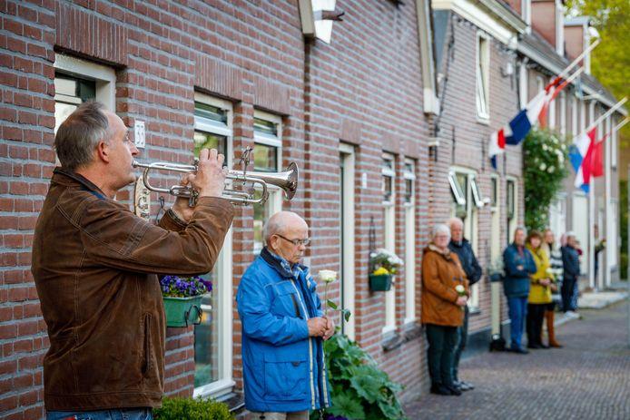 Bewoners met witte roos in de hand van de Visscherstraat luisteren naar het bekende taptoesignaal.