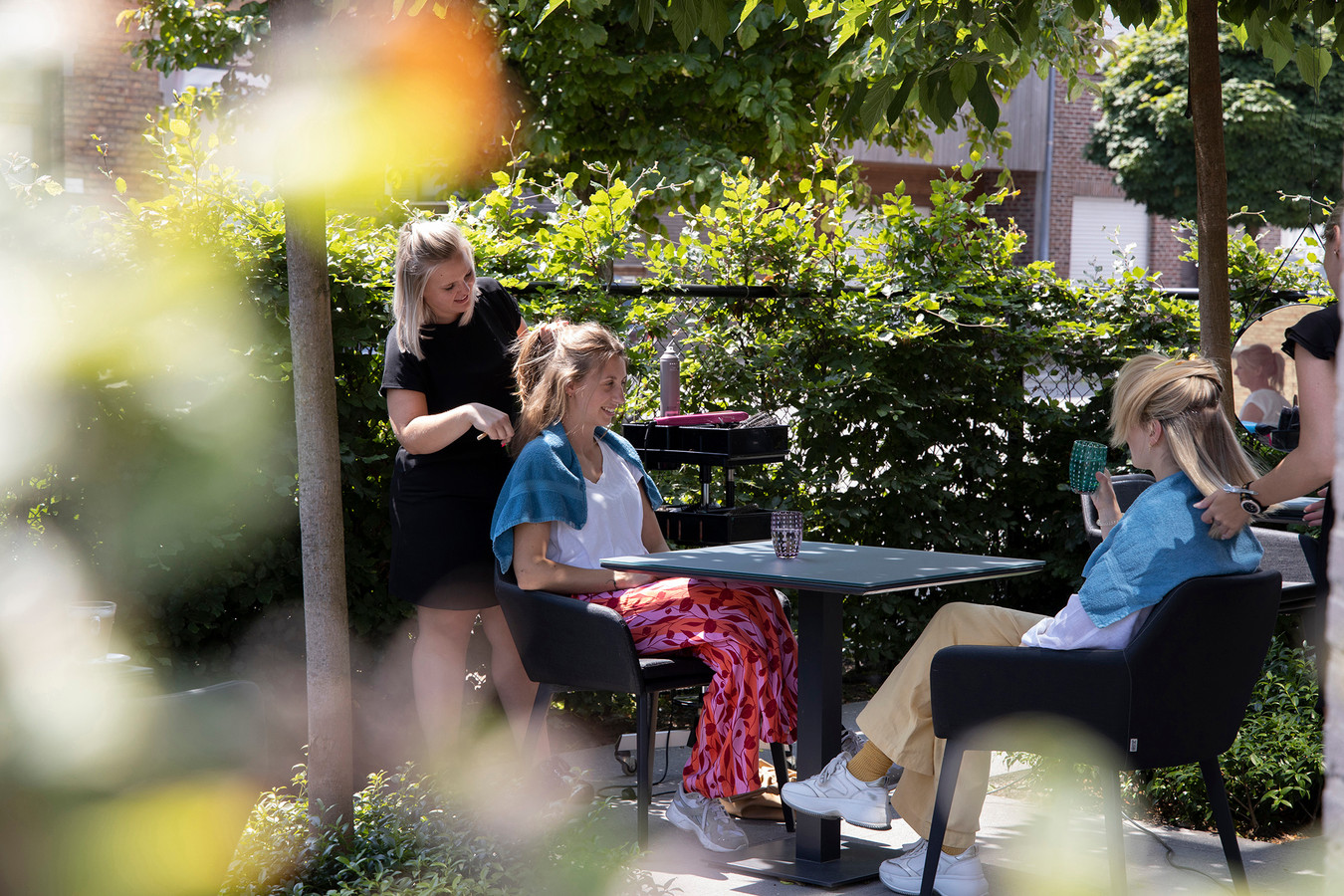 Een kapsalon in openlucht. Héérlijk, met dit zomerweer. Sunny Looks bevindt zich op het terras van Lucky Looks, aan de Oudenaardsesteenweg in Kortrijk.