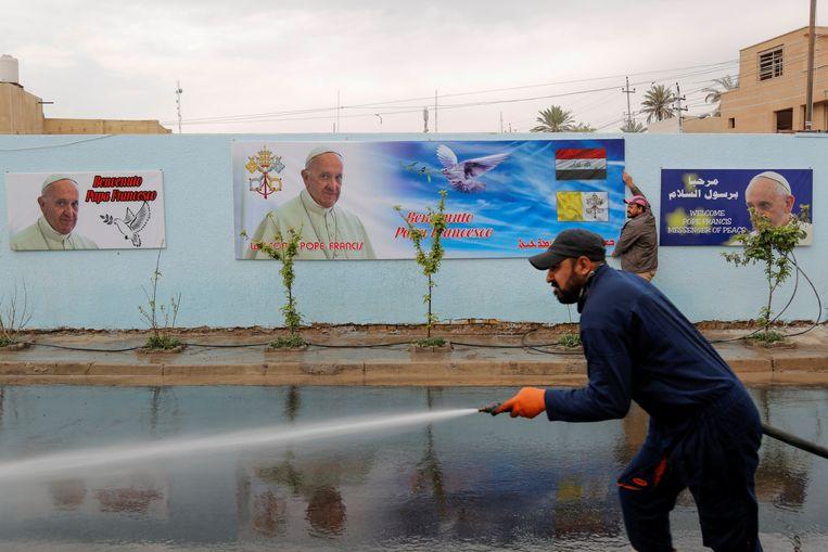 Een gemeentewerker maakt de straat schoon nabij de Sint-Jozef-kathedraal in Bagdad, waar de paus op zijn vierdaagse bezoek een mis zal leiden. Beeld REUTERS