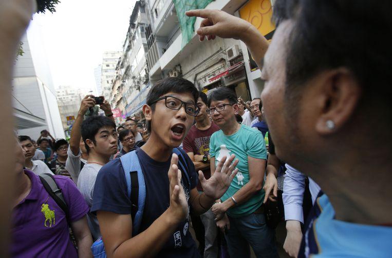 Een demonstrant probeert te onderhandelen met een boze buurtbewoner in de wijk Mong Kok. Beeld ap