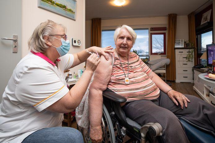 Hanny de Keijzer krijgt het vaccin toegediend door Anny van Velzen.