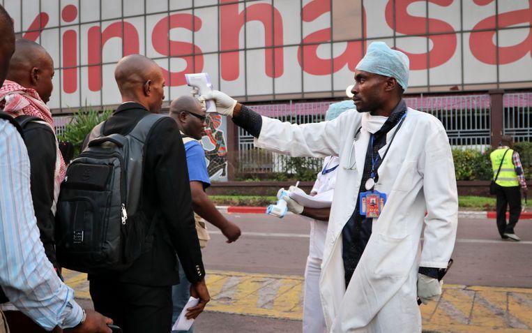 Een hulpverlener neemt de temperatuur op van passagiers die uit het vliegtuig in Kinshasa stappen. Beeld AP