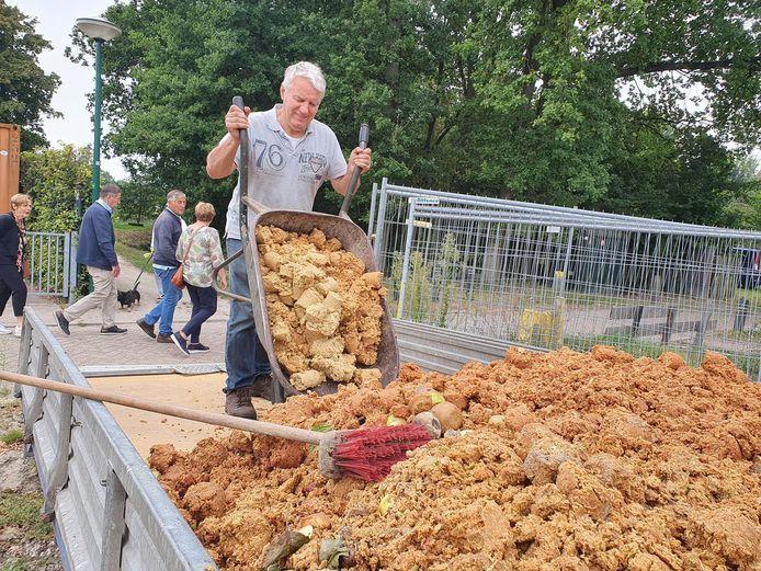 Voorzitter Mark Verhoeven van Natuurtuin 't Loo leegt een kruiwagen fruitpulp op de  aanhanger.