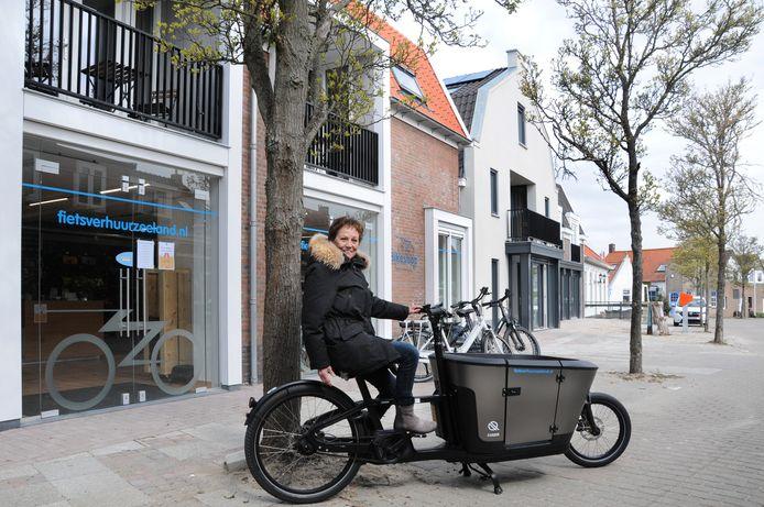 """De Scharendijkse dorpsraadvoorzitter Tanny de Rooij in de Dorpsstraat op één van de bakfietsen die Fietsverhuur Zeeland verhuurt. ,,De straat ziet er mooi uit en het wordt alleen nog maar beter."""" Na de zomer wordt ook de straat zelf heringericht."""