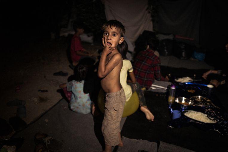 Vluchtelingen wat rest van kamp Moria. Slapen en eten doen ze op straat.  Beeld Zolin Nicola