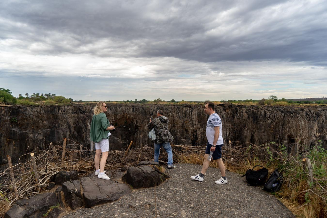 Toeristen reageren teleurgesteld als zij de drooggevallen waterval zien. Van de Victoria Falls, onderdeel van de lijst van werelderfgoed, is weinig meer over. FOTO ZINYANGE AUNTONY / AFP