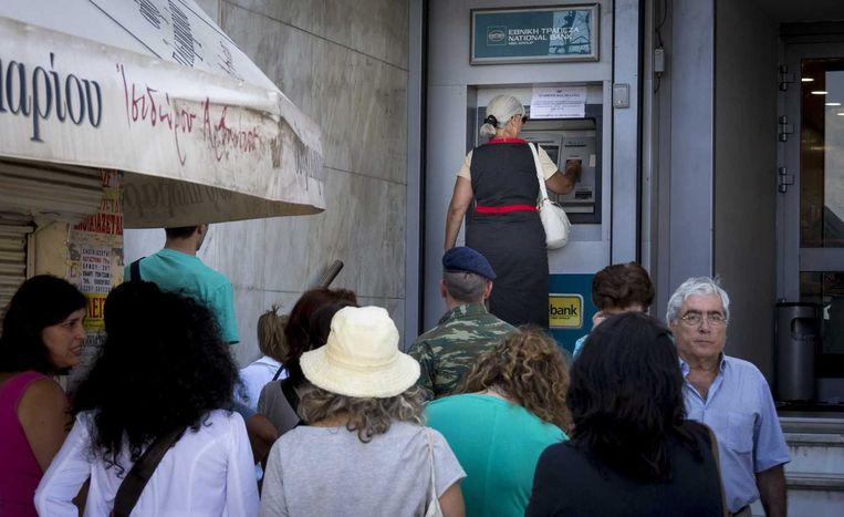 De Grieken staan dagelijks massaal in de rij om 60 euro te kunnen pinnen. Beeld anp