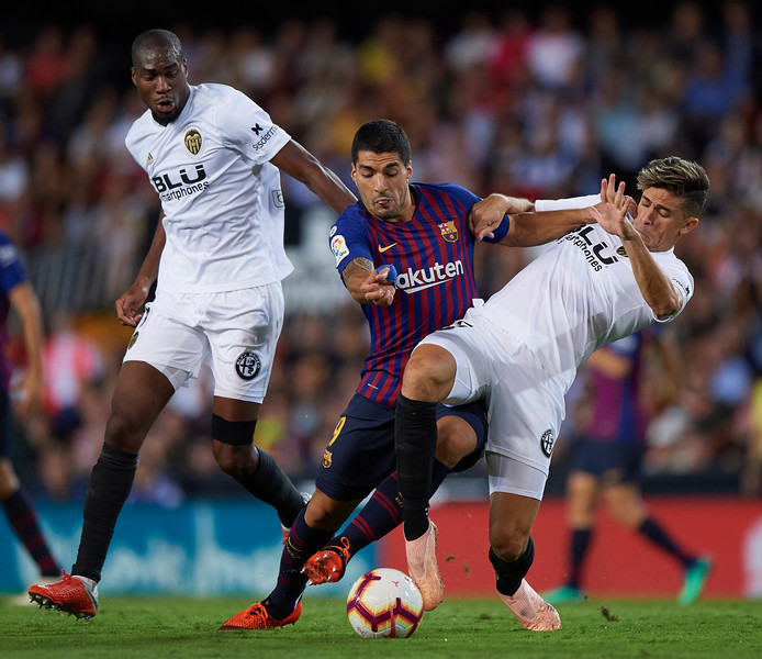 Geoffrey Kondogbia (l) namens Valencia in actie tegen FC Barcelona.