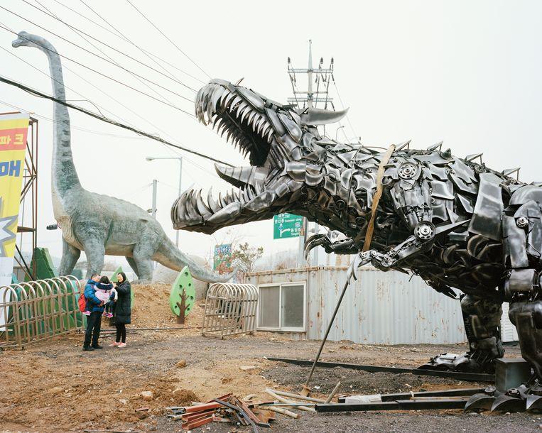 Aan het nieuwe dinosaurusthemapark wordt nog druk gewerkt, maar een jong gezinnetje komt alvast eens kijken.   Beeld Seunggu Kim/INSTITUTE