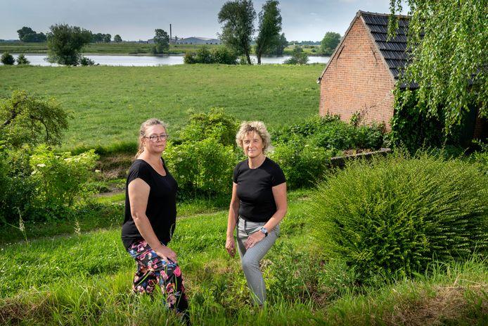 Barbara Maissan (links) en Anjo van Hemert op de Maasdijk bij Well. Aan de overkant, bij de steenfabriek, komen mogelijk vier windmolens van 240 meter hoog.